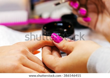 Young beautiful woman in a nail salon receiving a manicure by a professional beautician  - stock photo
