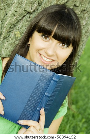 Young beautiful woman in a park with a notebook.