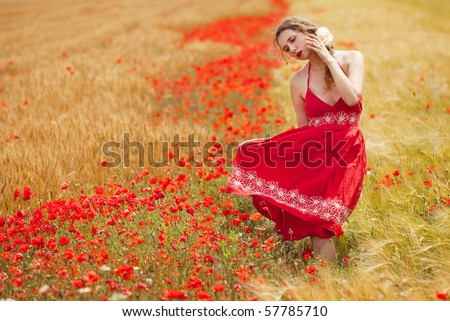 young beautiful woman in a poppy field in summer - stock photo