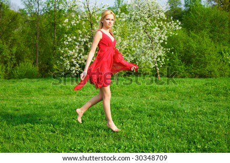 Young beautiful woman in a red dress running in green meadow - stock photo