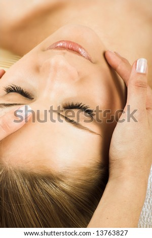 young beautiful woman in a spa is getting a massage - stock photo