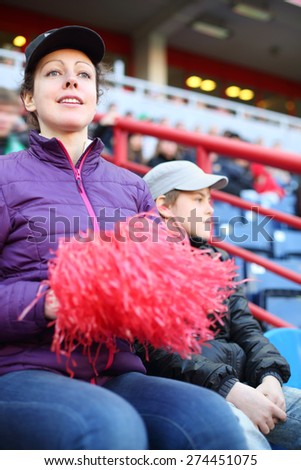 Young beautiful woman in a sports jacket and a cap and boy at stadium - stock photo