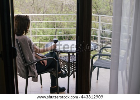 Young beautiful woman in a sweater sitting on a cozy terrace with a glass of red wine - stock photo