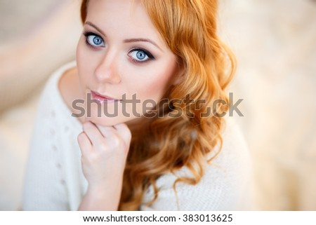 Young beautiful woman in a warm pullover in a light bedroom in a morning. Close up portrait, blue eyes and natural makeup - stock photo