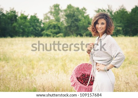 Young beautiful woman in a wheat field with cherries basket.