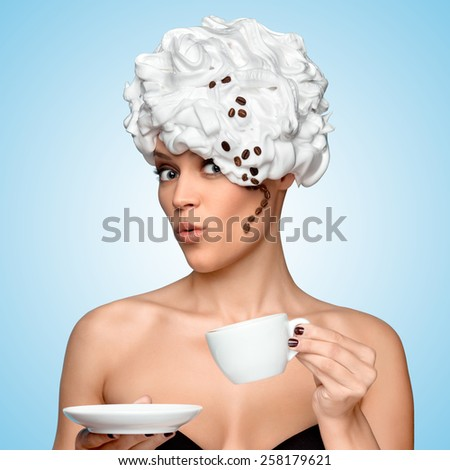 Young beautiful woman in a whipped cream with a curl made of roasted coffee beans on her head, drinking coffee and holding a coffee cup on blue background. - stock photo