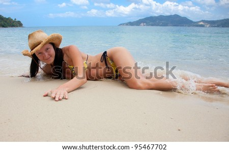 Young beautiful woman in a yellow bikini on the beach