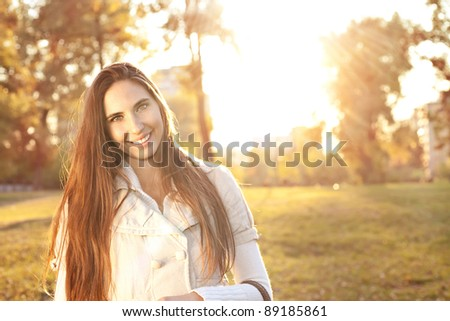 Young beautiful woman in an autumn park with sunlight
