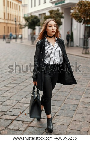Young beautiful woman in autumn coat with stylish bag, shoes, striped blouse on the street