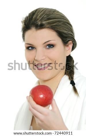 Young beautiful woman in bathrobe eating an apple - stock photo