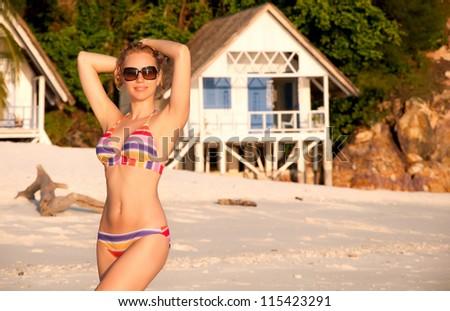 Young beautiful woman in bikini at the beach during sunset - stock photo