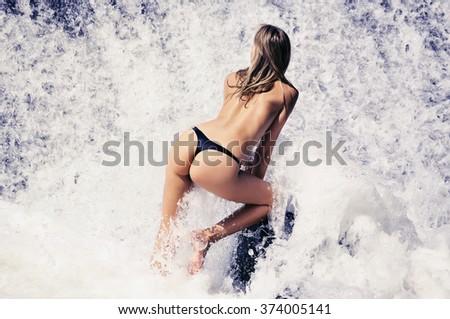 Young  beautiful woman in bikini standing in the water foam at the river waterfall. - stock photo