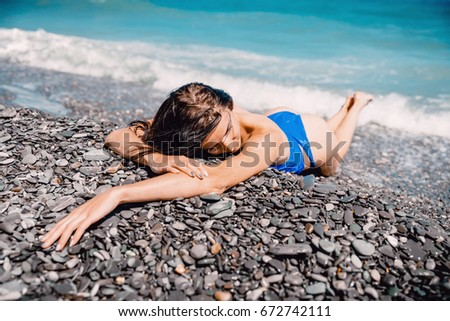 Young beautiful woman in bikini swimsuit relaxed on beach, tropical island, summer vacation