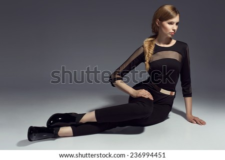 young beautiful woman in black bodysuit and black shoes - stock photo