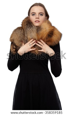 Young beautiful woman in black dress with a fox collar - stock photo