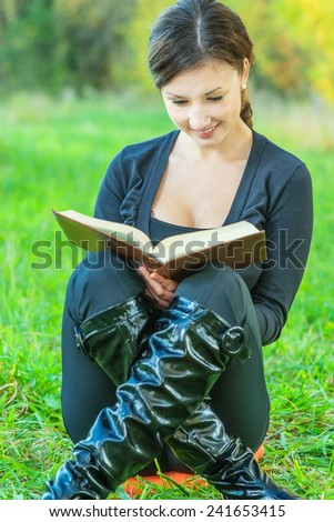 Young beautiful woman in black jacket reads book against autumn nature. - stock photo