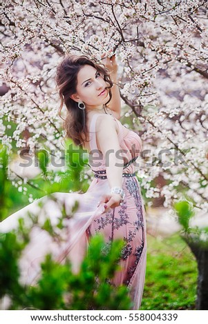 Young beautiful woman in blooming garden.