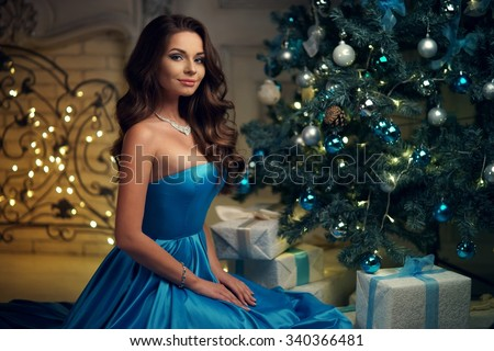 Young beautiful woman in blue elegant evening dress sitting on floor near christmas tree and presents on a new year eve. Interior with christmas decorations. Shallow DOF and bokeh background - stock photo