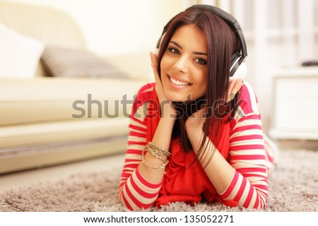 Young beautiful woman in bright outfit enjoying the music at home - stock photo