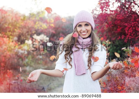 Young beautiful woman in colorful autumn leaves - stock photo