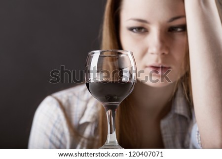 Young beautiful woman in depression, drinking alcohol on dark background - stock photo