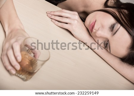 Young beautiful woman in depression, is drinking alcohol. - stock photo