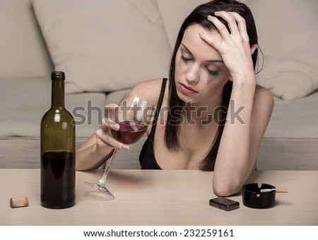 Young beautiful woman in depression, is drinking alcohol and smoking. - stock photo