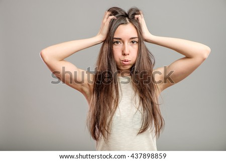 Young beautiful woman in depression isolated on gray background - stock photo