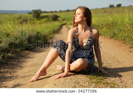 young beautiful woman in dress sitting on the road