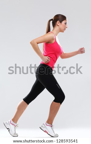 Young beautiful woman in fitness wear runs isolated over background - stock photo
