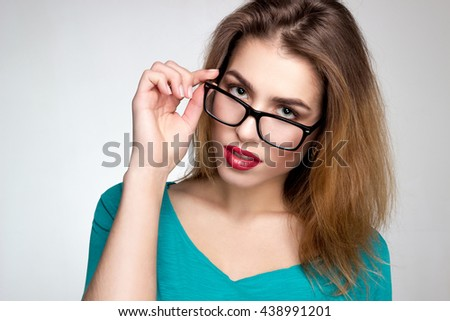 Young beautiful woman in glasses and with red lips looking at the camera in studio on grey background