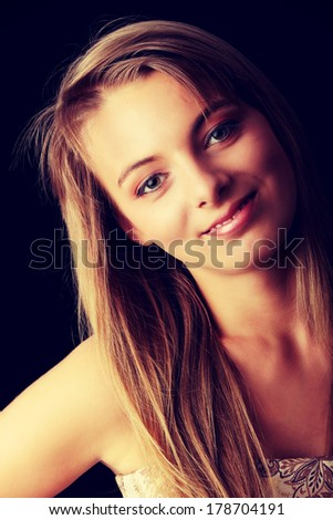 Young beautiful woman in gold dress portrait isolated on black background - stock photo