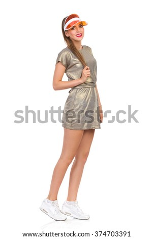 Young beautiful woman in gold mini dress, sneakers and orange plastic cap. Full length studio shot isolated on white. - stock photo