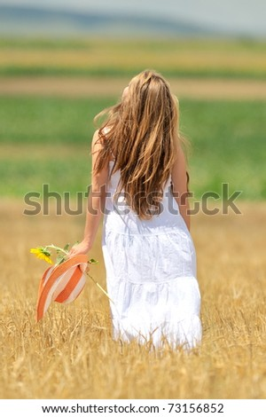 young beautiful woman in golden cereal field - stock photo