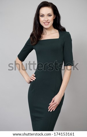 Young beautiful woman in green dress posing on grey background  - stock photo