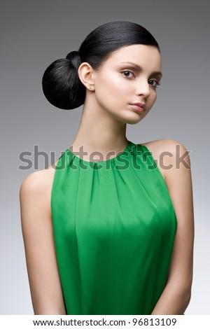 young beautiful woman in green dress, studio shot - stock photo