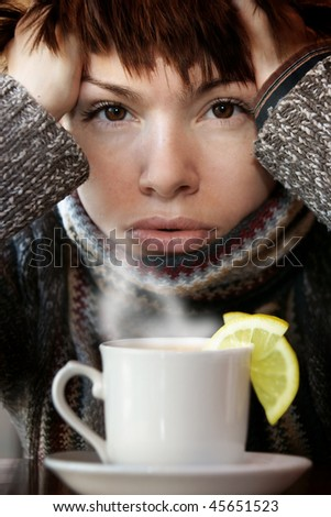 young beautiful woman in knitted scarf,  with the cup of hot tea - stock photo