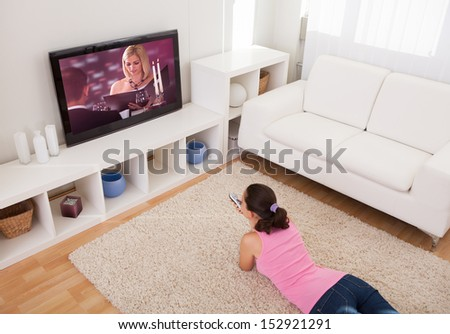 Young Beautiful Woman In Living Room Watching Television - stock photo