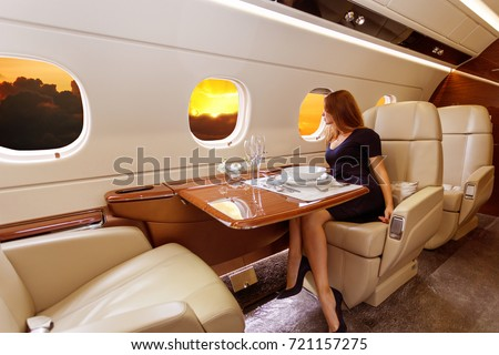 young beautiful woman in Luxury interior in bright colors of genuine leather in the business jet, sky and rays of sunset through the porthole