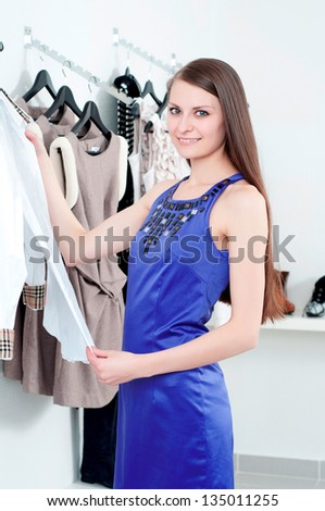 young Beautiful woman in mall buying clothes - stock photo