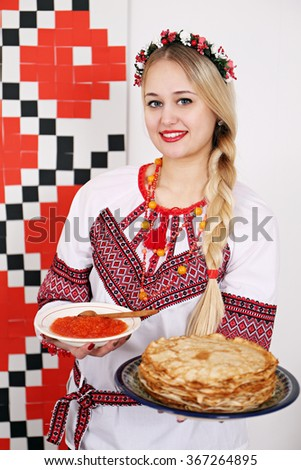 Young beautiful woman in national costume holding a plate of pancakes and red caviar. Background for shrovetide - stock photo