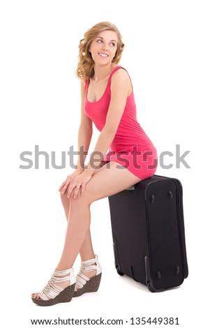 young beautiful woman in pink dress sitting on big suitcase over white background