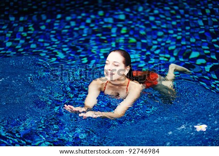 Young beautiful woman in pool in luxury hotel in Bali, Indonesia - stock photo