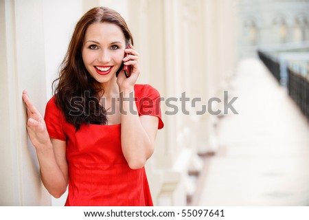 Young beautiful woman in red dress talks on cellular telephone against big hall. - stock photo