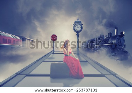 Young beautiful woman in red dress waiting old train on the platform of railway station. Dreamy foggy screen saver. Retro style vintage Instagram picture. Vacation voyage getaway adventure concept  - stock photo