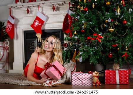 Young beautiful woman in red dress with gift lies near Christmas tree at home. New year and Christmas. - stock photo