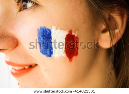 Young beautiful woman in red dress with painted french flag football supporter fan - stock photo