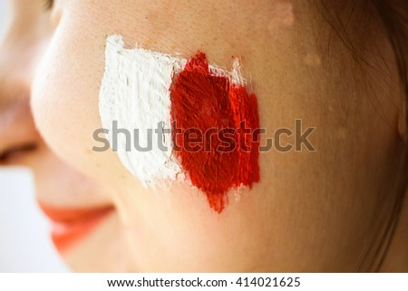 Young beautiful woman in red dress with painted red & white flag football supporter fan - stock photo