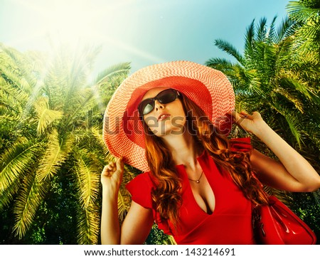 Young beautiful woman in red fashion dress, big hat and sun glasses on tropical resort - stock photo
