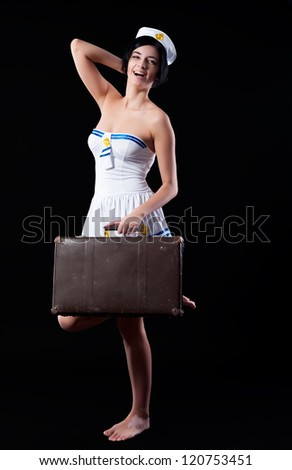 Young beautiful woman in sailor costume with old suitcase - stock photo
